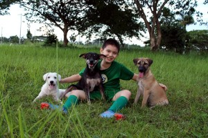 Ken with White Puppy, Blackie and Brownie after months of caring in the Happy Animals Club. Image via Happy Animals Club.