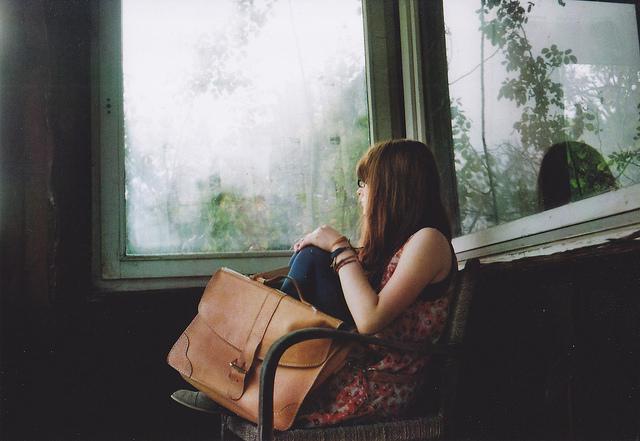 girl sitting pensive alone